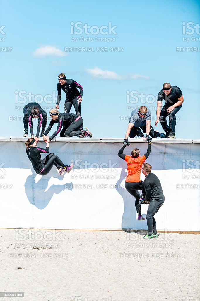 Teamwork with people on obstacle course run stock photo