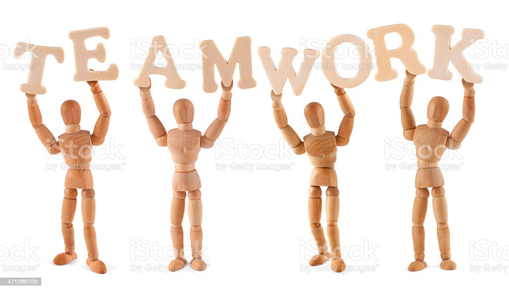 Teamwork - wooden mannequin holding this word stock photo