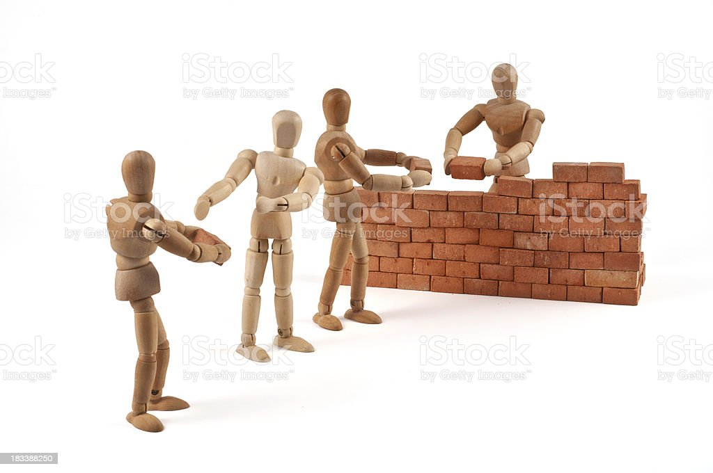 Teamwork - wooden mannequins building a wall stock photo