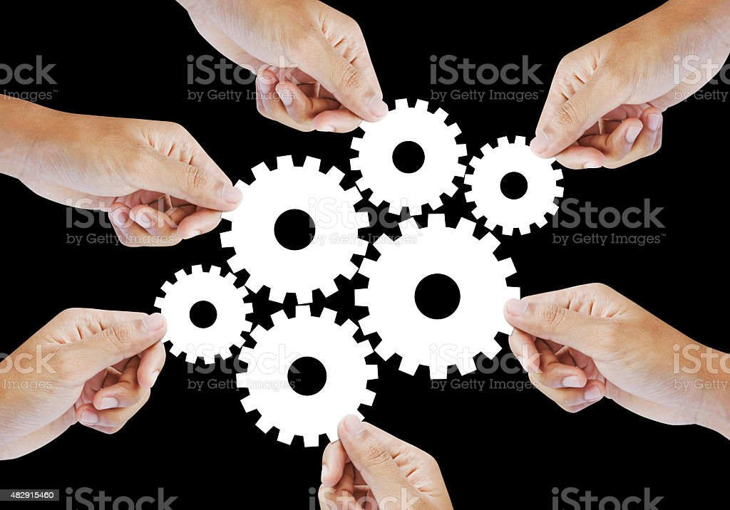 Teamwork works together to build a cog wheel gear system stock photo