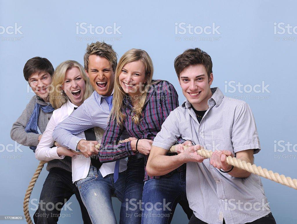 Teamwork: young people playing tug-of-war stock photo