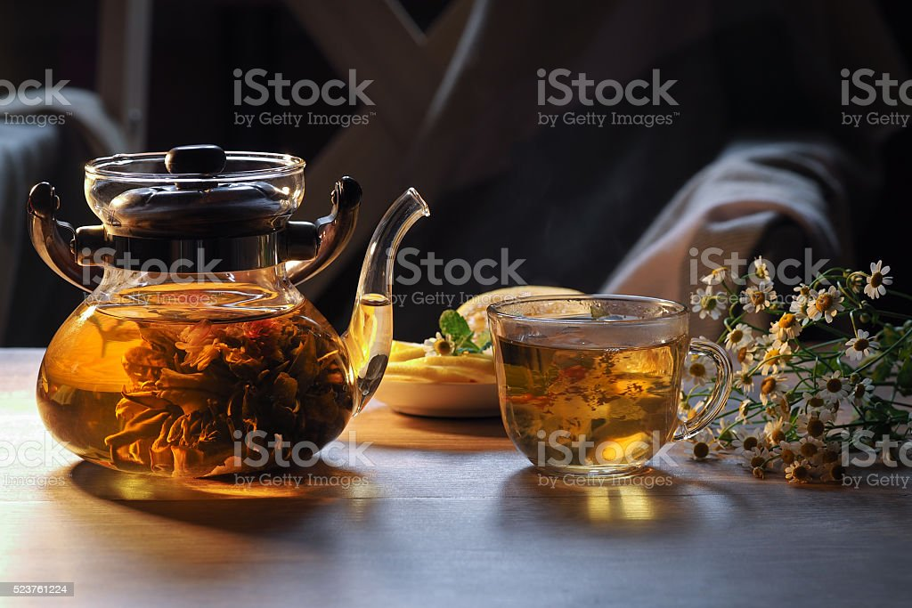 Teapot and glass cup with blooming tea flower inside stock photo