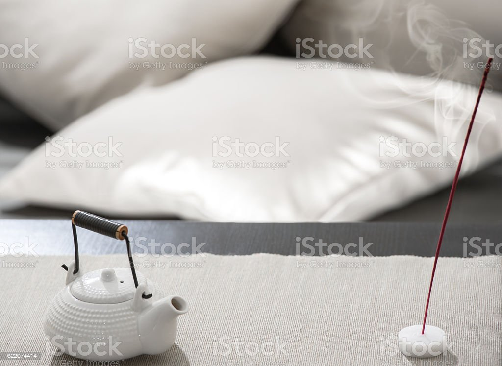Teapot and incense stick on table at relaxation lounge stock photo