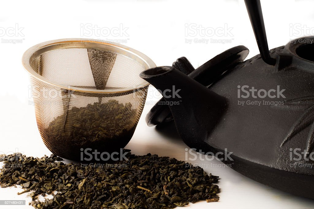 Teapot and tea leaves stock photo