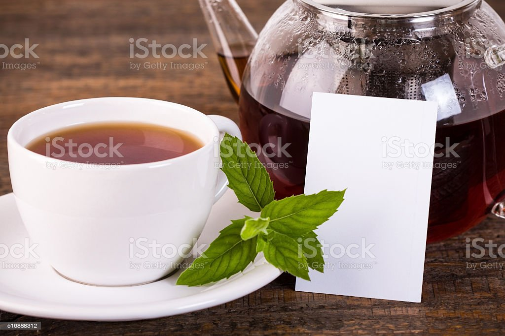 Teapot and white cup with white label stock photo