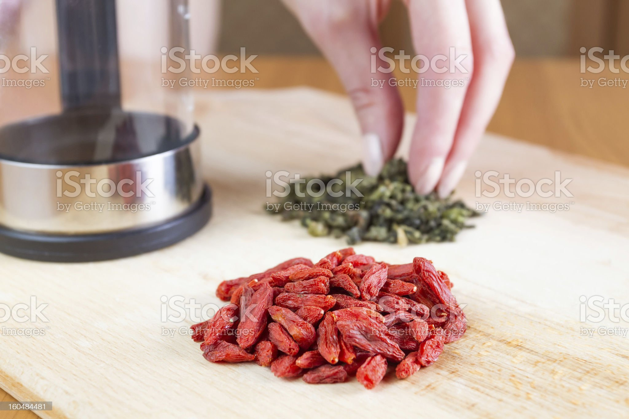 Teapot, green tea, goji on the table closed up royalty-free stock photo