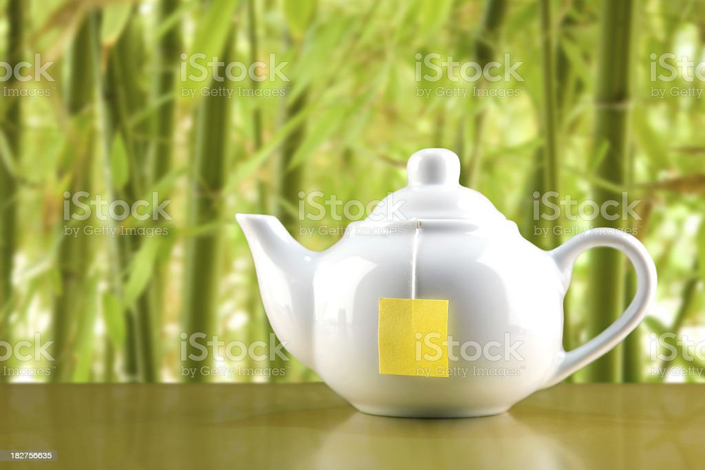 Teapot on green background royalty-free stock photo