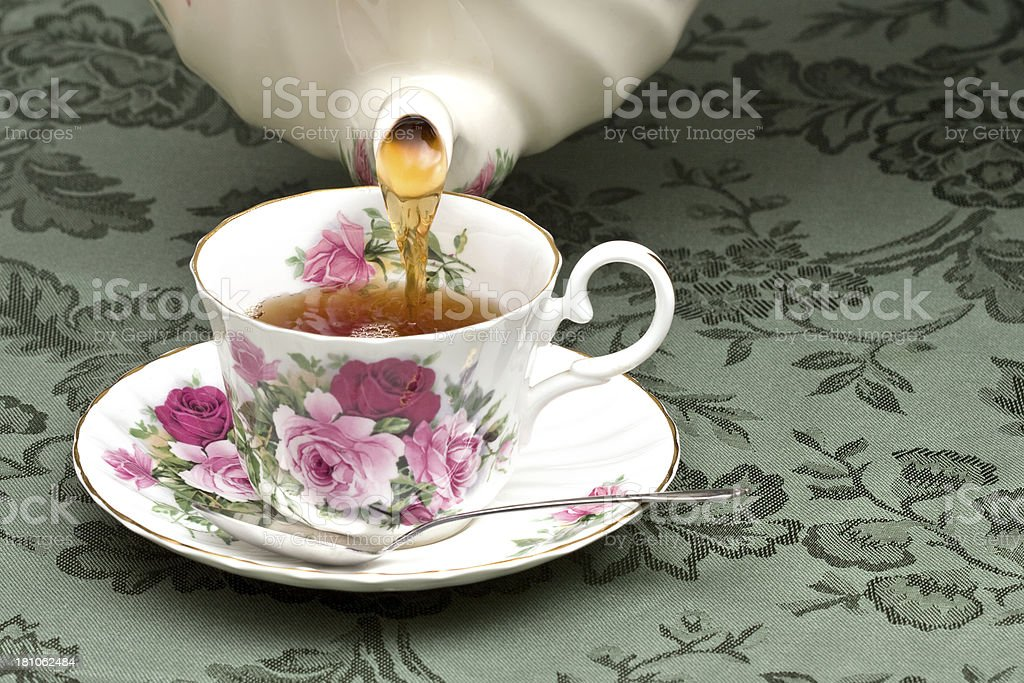 Teapot pouring tea into a cup royalty-free stock photo