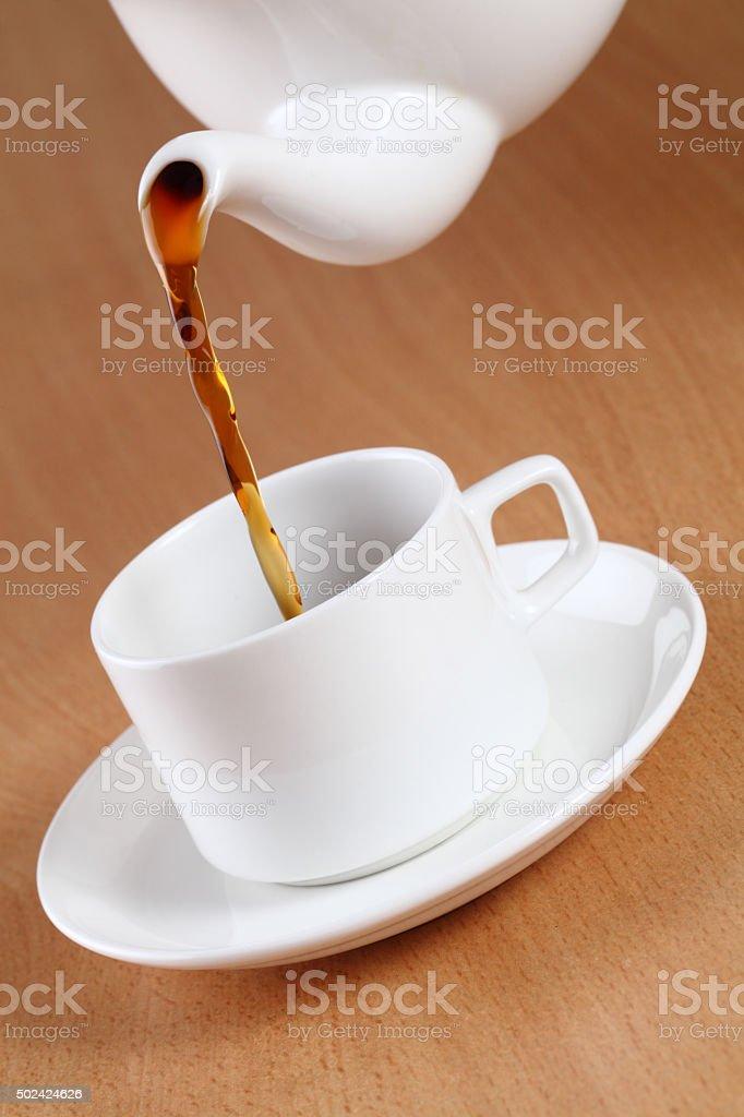 Teapot pouring tea into a cup stock photo