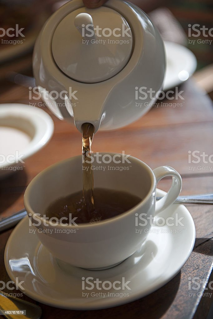 Teapot pouring tea into cup and saucer stock photo