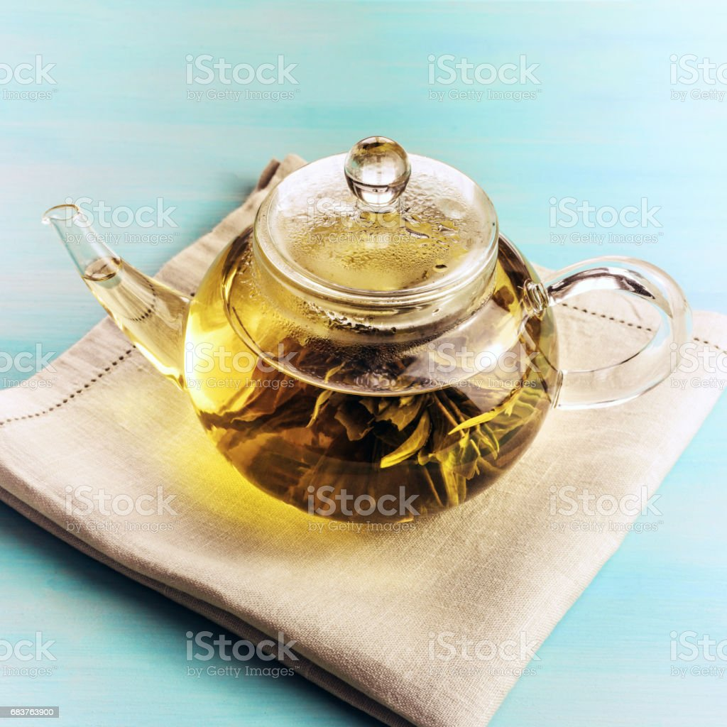 Teapot with tea flower on teal background stock photo