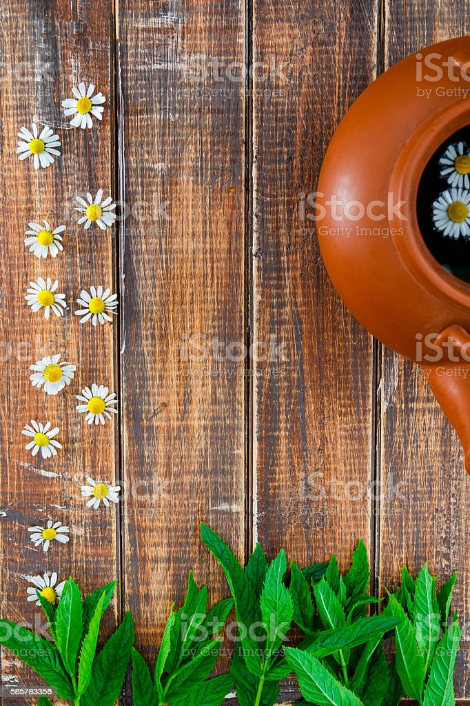 teapot with tea near flower of chamomile and fresh mint stock photo