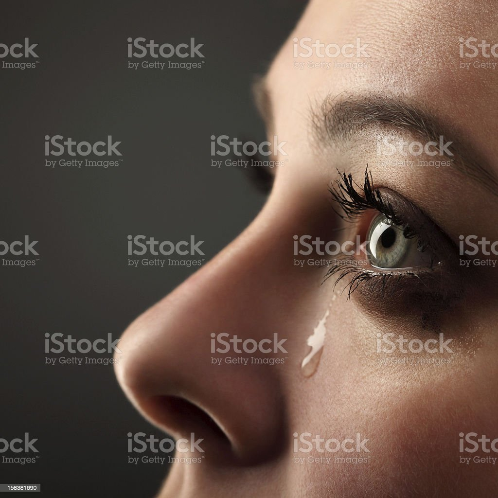 Teardrop falling from woman's eye stock photo