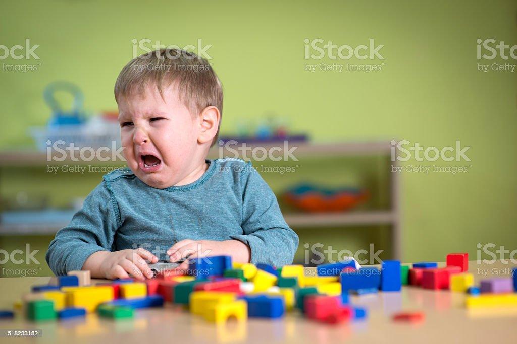 Tearful boy in nursery with Montessory toys stock photo
