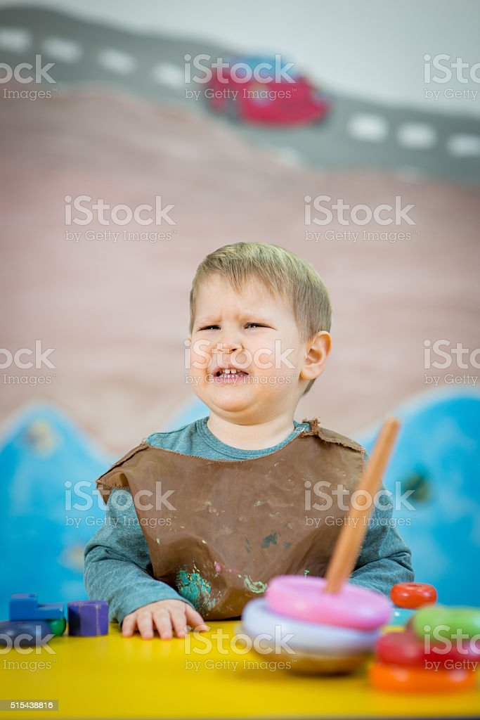 Tearful spoiled boy in nursery with Montessory toys stock photo
