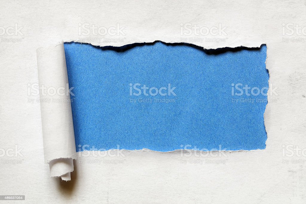 Tearing a paper frame hole with blue background stock photo