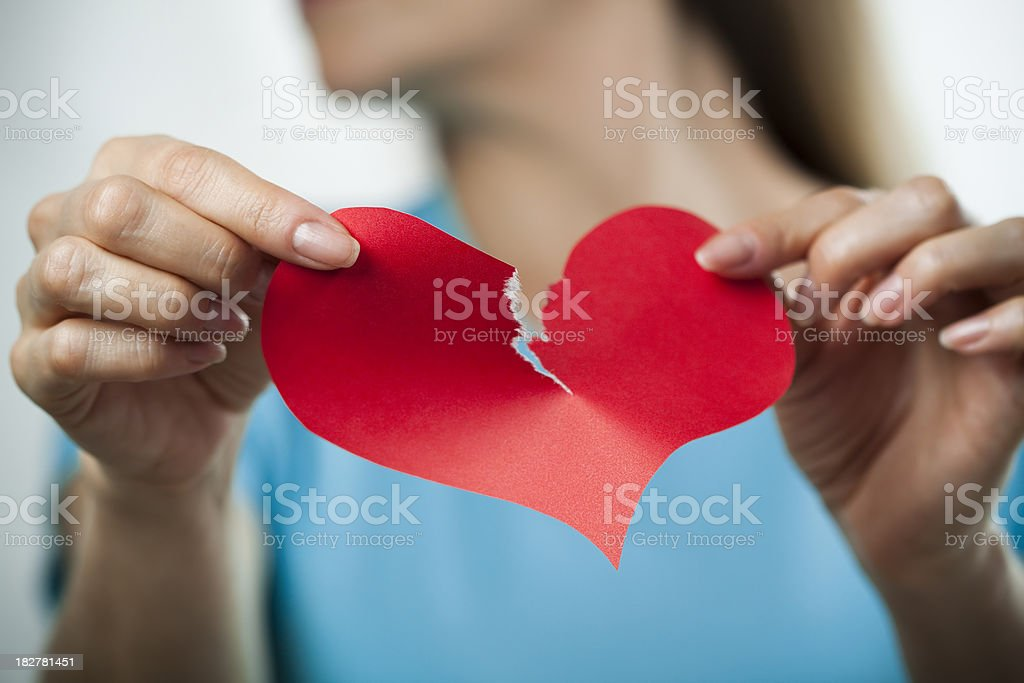 Tearing up a paper heart, breakup concept stock photo