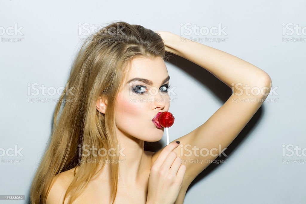 Teasing young blonde girl portrait with sugar candy stock photo