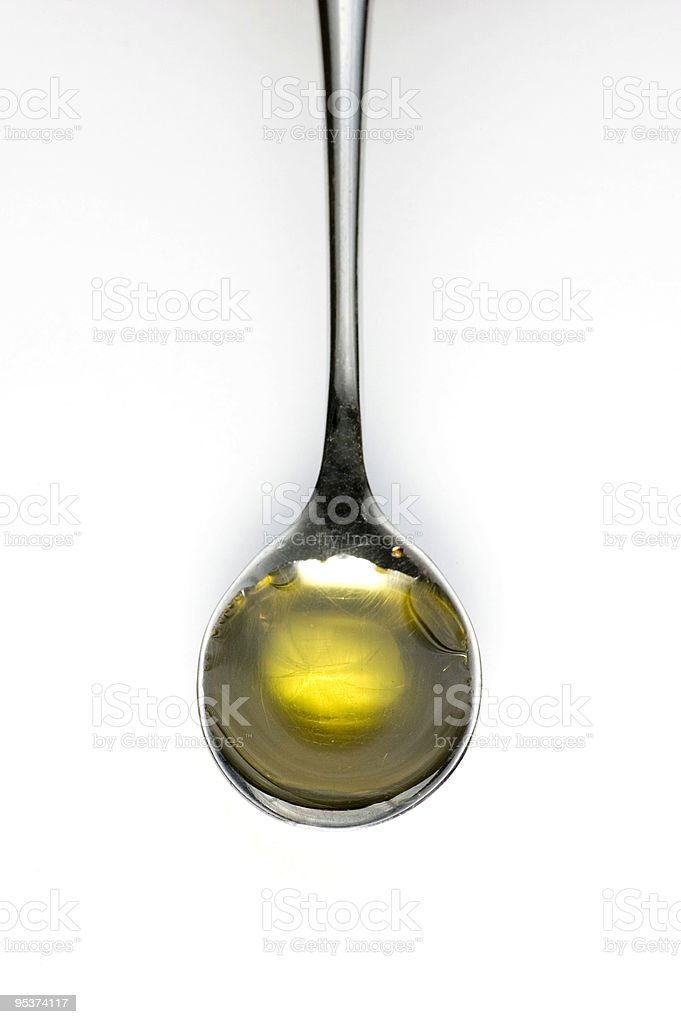 Teaspoon of olive oil isolated on white background royalty-free stock photo