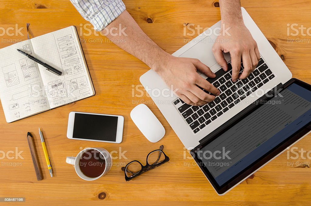 Tech Hipster Working at Wooden Desk on Laptop stock photo