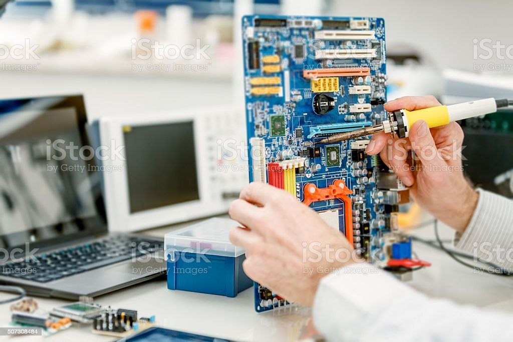 Tech tests electronic equipment in service centre stock photo
