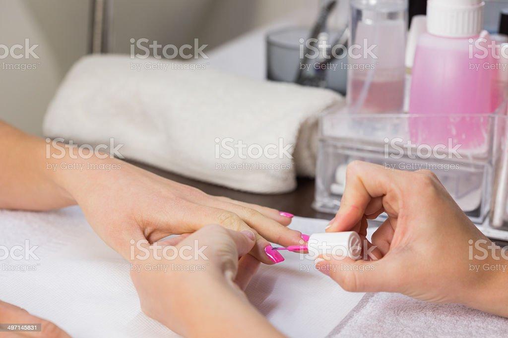 Technician applying pink nail varnish to finger nails stock photo