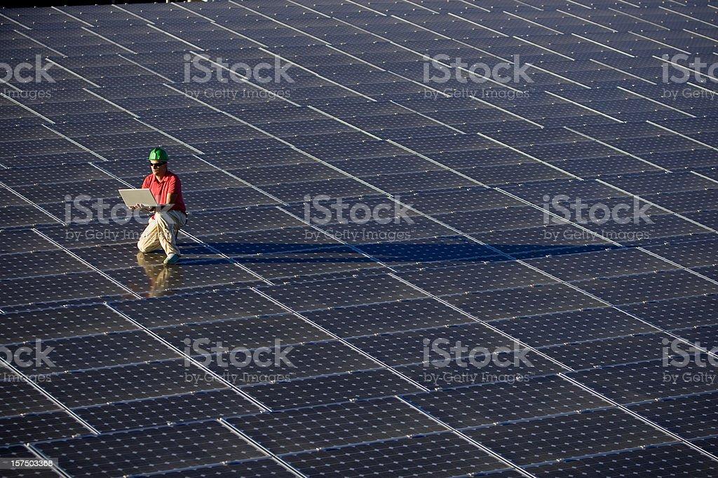 Technician at a photovoltaic farm royalty-free stock photo