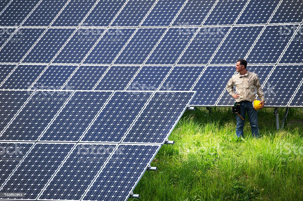 Technician at ground solar panel field stock photo