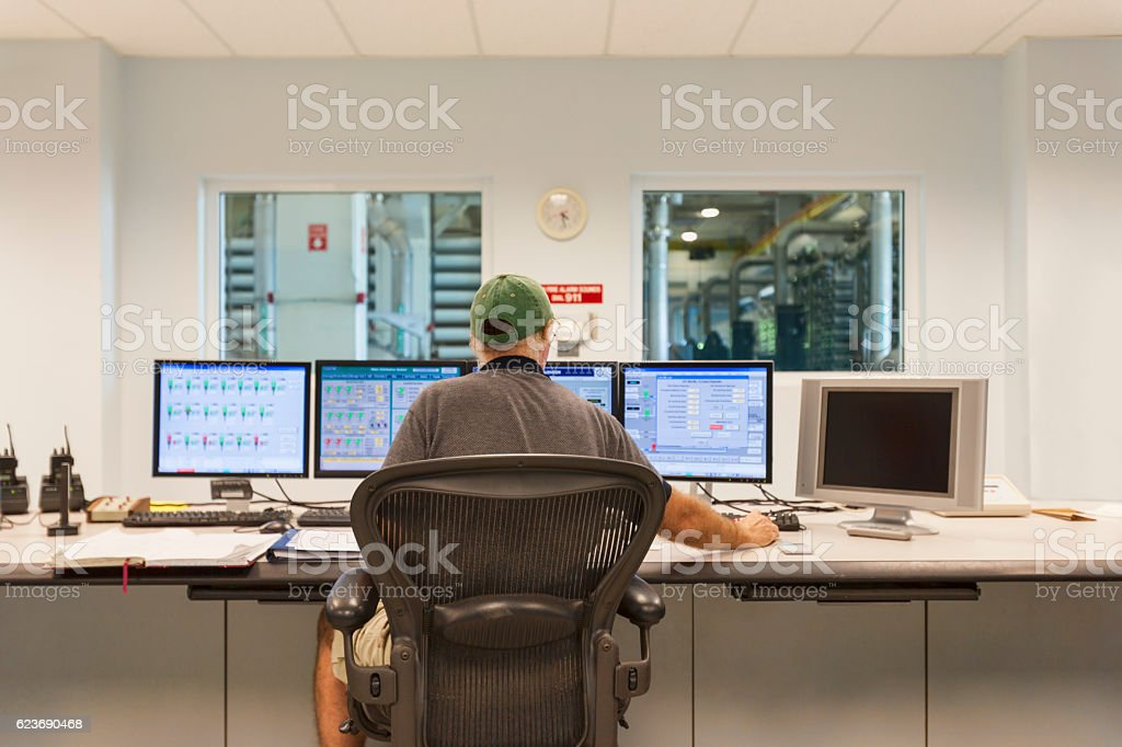Technician at the Computers in a Control Room stock photo