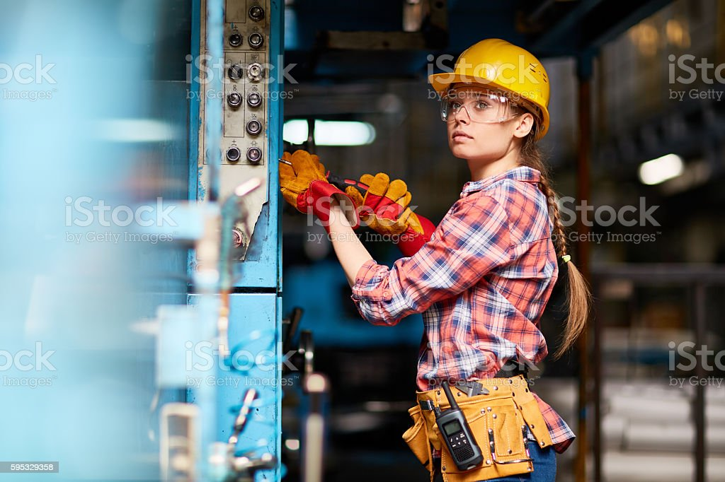 Female technician in hardhat and protective eyeglasses at work