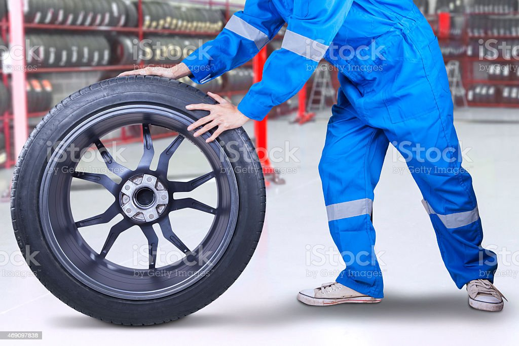 Technician changing a tire at workshop stock photo