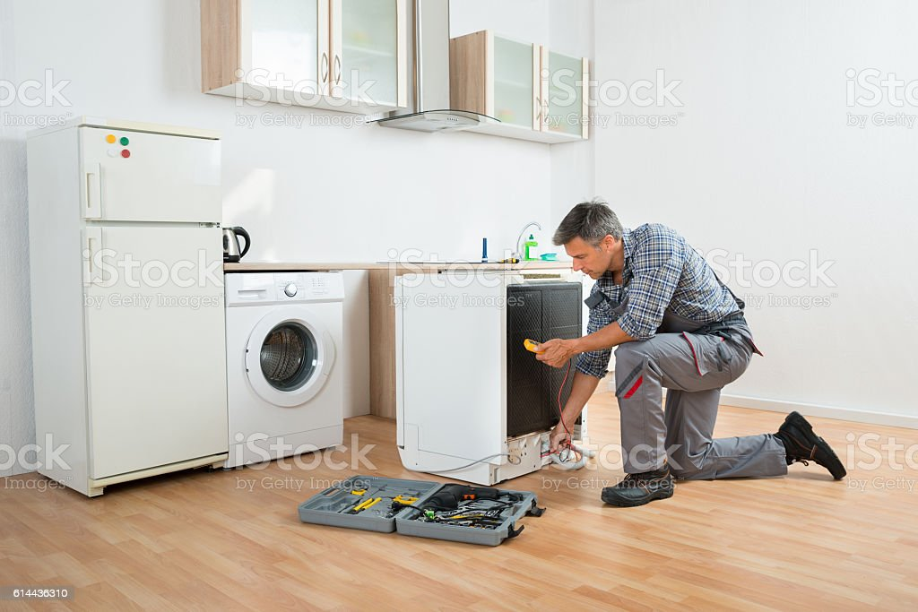 Technician Checking Dishwasher With Digital Multimeter stock photo