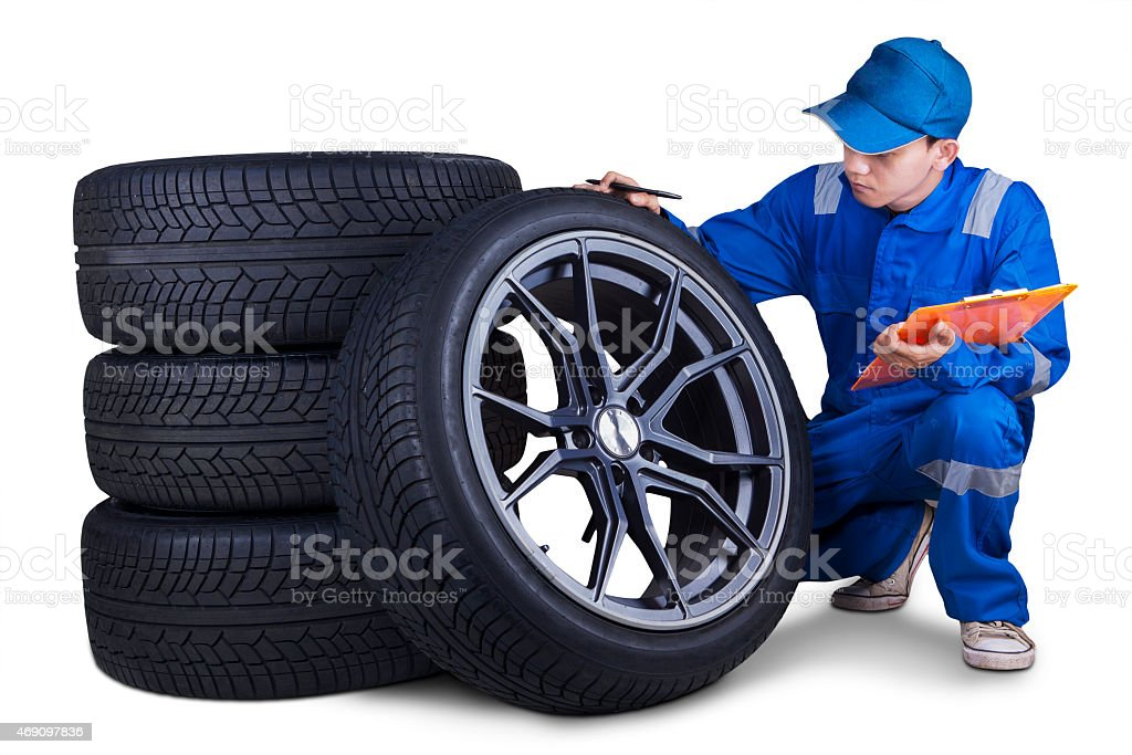 Technician checking tires isolated stock photo