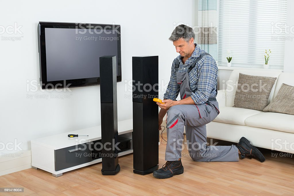 Technician Checking TV Speaker With Multimeter stock photo