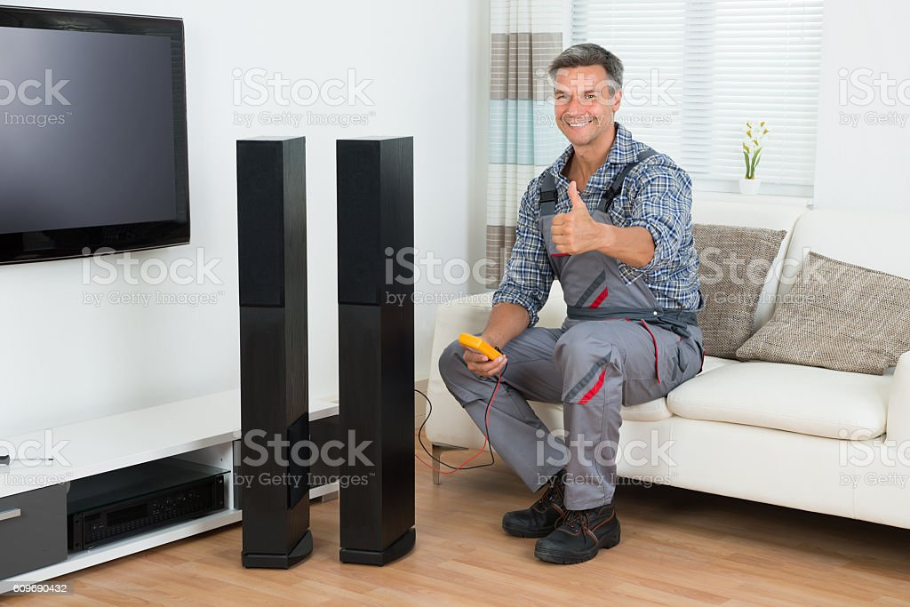 Technician Checking TV Speaker With Multimeter stock photo
