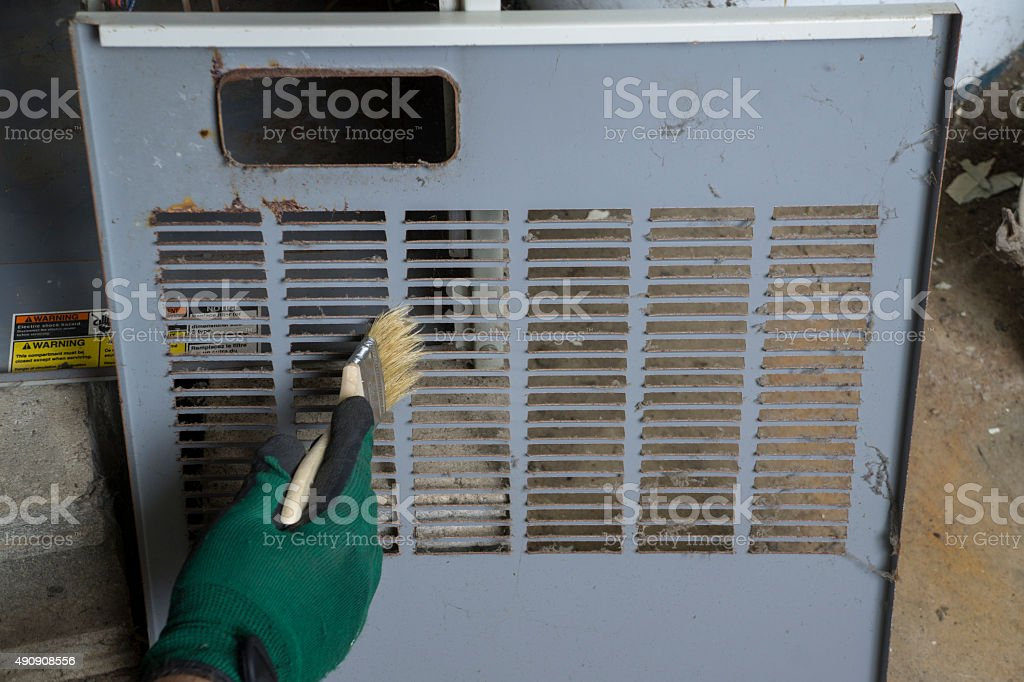 Technician Cleaning Front Cover Of Furnace stock photo