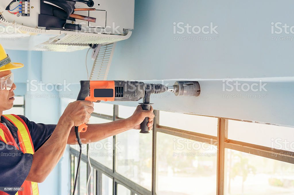 Technician drilling the wall with Impact drill install Repairing stock photo