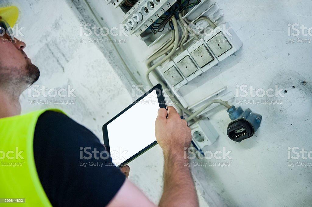 Technician Examining Fusebox Using Tablet stock photo