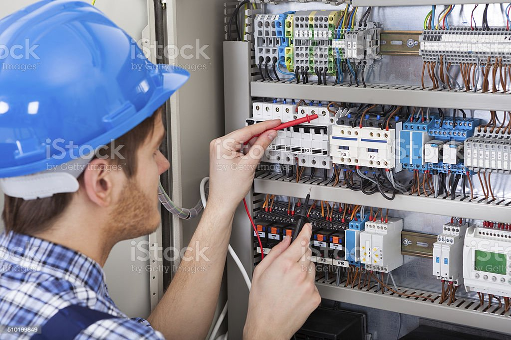 Technician Examining Fusebox With Multimeter Probe stock photo