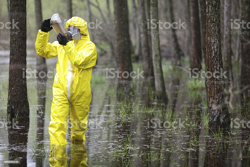 technician examining sample of water  in floods area stock photo