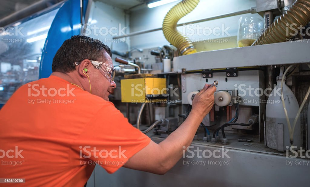 Technician fixing a machine at a factory stock photo