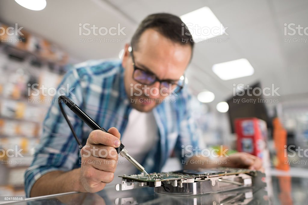 IT technician fixing a motherboard stock photo