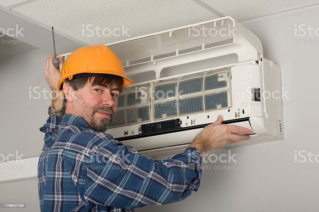 Technician fixing air conditioner royalty-free stock photo