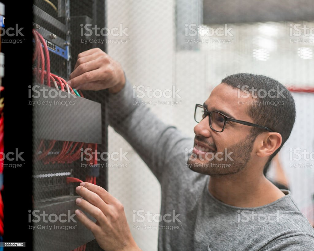IT technician fixing cables at the office stock photo