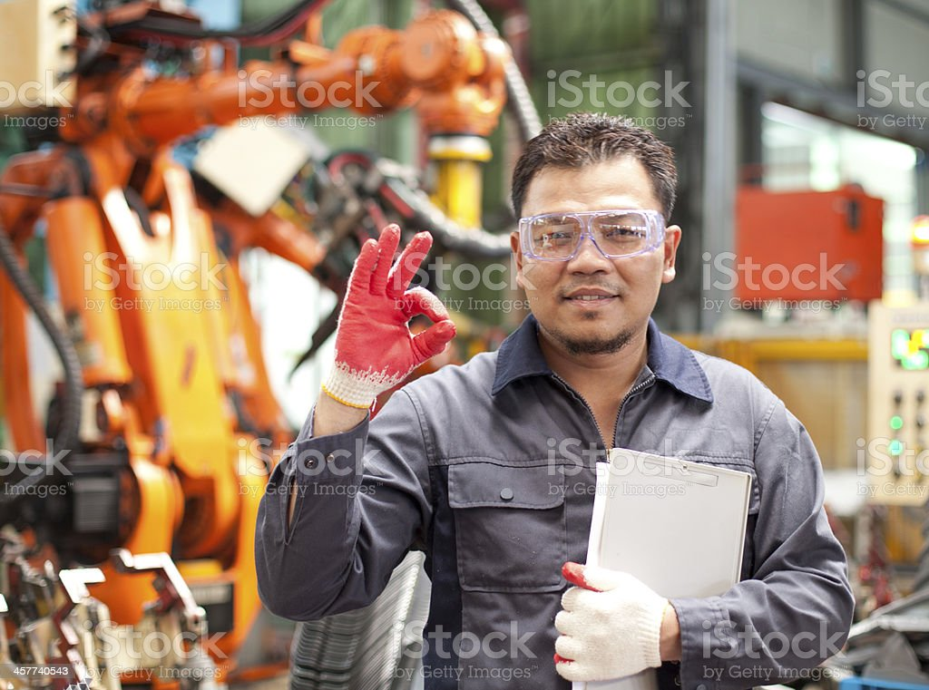 Technician giving the OK sign in a factory stock photo