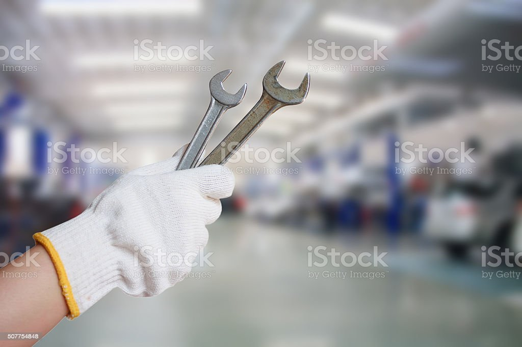 Technician holding a wrench with car repair service center background stock photo