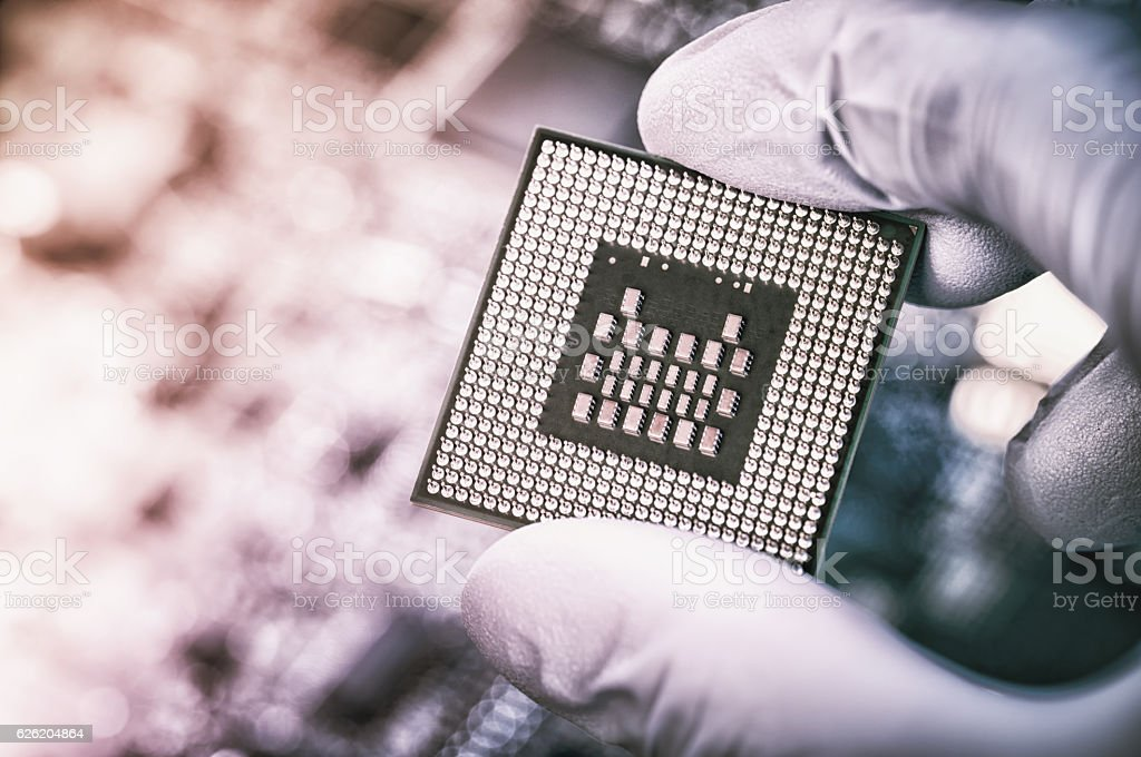 Technician holding big chip over defocused circuit board stock photo