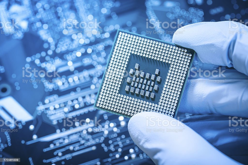 Technician holding chip over blue circuit board stock photo
