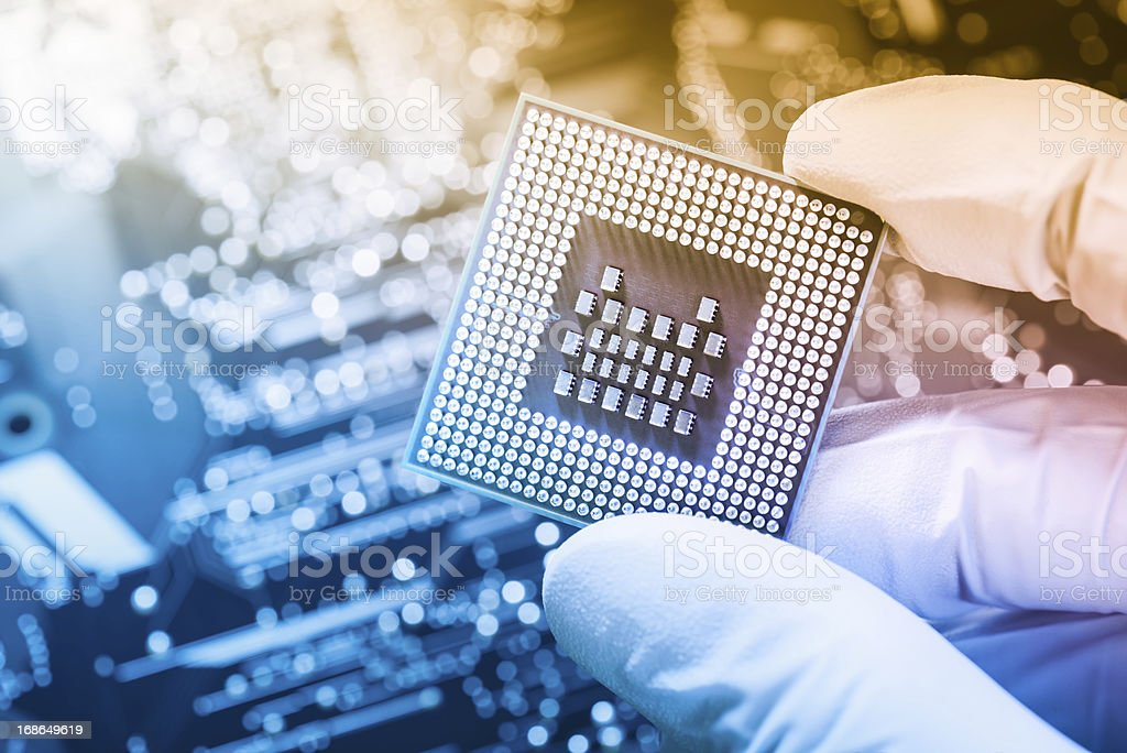Technician holding chip over defocused circuit board stock photo