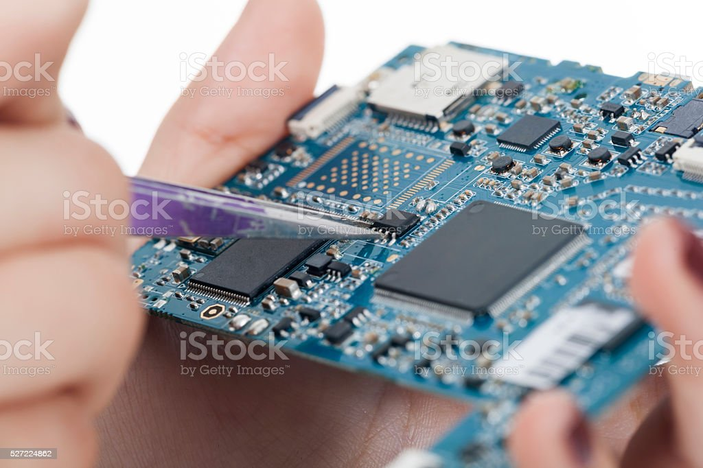 Technician holding chip with woman hand in tweezers stock photo